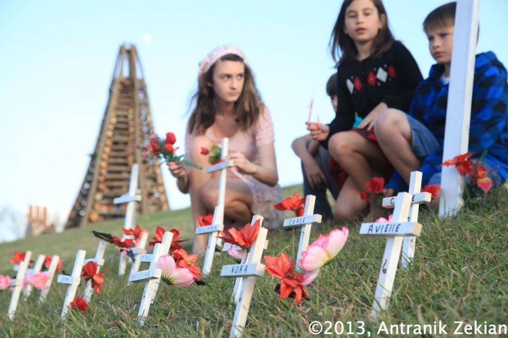 des enfants entrain d'installer de petites croix en mémoire des victimes de Newtown